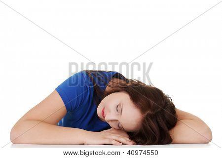 Sleeping while learning - tired teen woman sleeping on desk