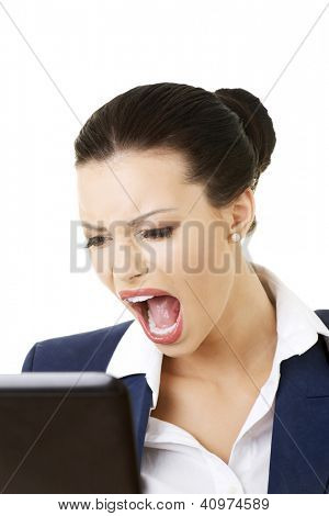 Angry businesswoman shouting on her laptop, isolated on white