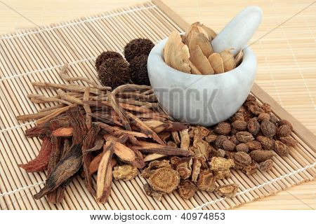 Chinese herbal medicine selection in a marble mortar with pestle and loose over bamboo mats.