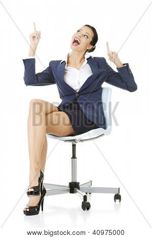 Attractive happy businesswoman sitting on office chair and showing copy space. Isolated on white.