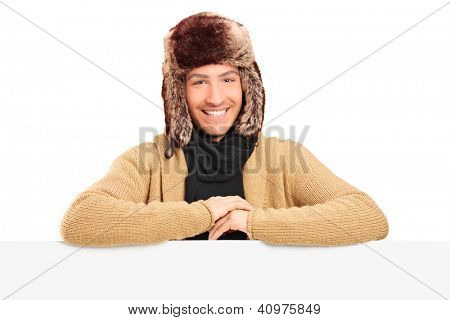 Handsome young man with fur hat posing behing a blank panel isolated on white background