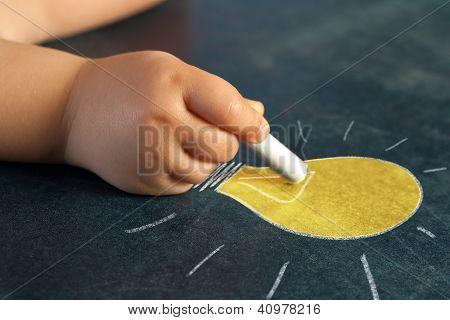 Infant Hand Drawing A Light Bulb.