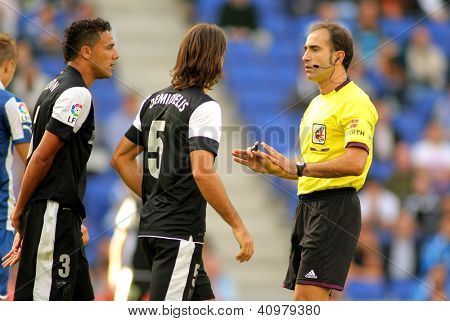 BARCELONA - OCT, 27: Demichelis and Welington of Malaga discuss with the referee Delgado Ferreiro during a Spanish match against Espanyol at the Estadi Cornella on October 27, 2012 in Barcelona, Spain