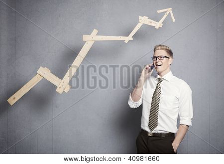 Concept: Successful business. Confident young businessman on the mobile-phone in front of rising business graph, isolated on grey background.