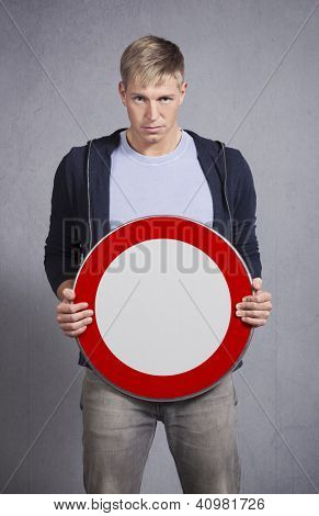 Serious man holding universal forbidden sign with space for text isolated on grey background.