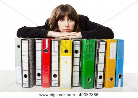 Exhausted woman in the office resting over  the folders, isolated on white background