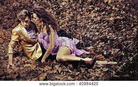 Couple lying on autumn leaves