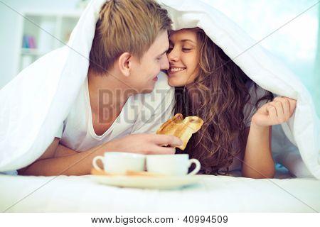 Desfrutando de um outro ao ter o pequeno-almoço na cama de casal