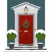 stock photo of planters  - Traditional red-painted front door with snow and a festive Christmas wreath of evergreen and berries. Brass door furniture  including bell-pull, letterbox and a lantern. Clipped  topiary bay trees in decorative planters standing on the entrance steps.