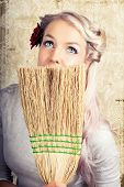 image of nineteen fifties  - Beautiful retro nineteen fifties housewife sitting daydreaming looking up at the ceiling with a faraway expression while holding a straw broom concealing the lower portion of her face - JPG