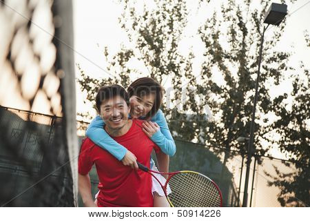 Boyfriend holding his girlfriend next to the tennis net
