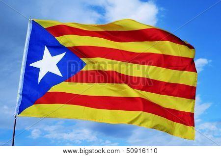 an estelada, the Catalan separatist flag, waving over the blue sky