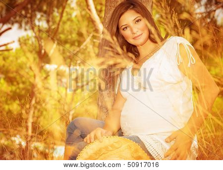 Pregnant woman in autumn park, beautiful expectant female relaxing outdoors in sunny autumnal day, happy and healthy pregnancy concept