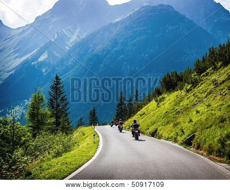 Moto racers riding on mountainous road, drive a motorcycle, summer adventure, extreme sport, travel to Europe, active lifestyle, vacation concept