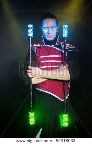 Performance of a man with a terrible pupils in samurai garb with glow sticks