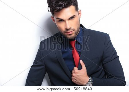 closeup of an elegant young fashion man in tuxedo holding his lapel while looking into the camera. on gray background