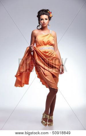 full length photo of a young fashion woman lifting up her dress with a hand while looking into the camera. on gray background