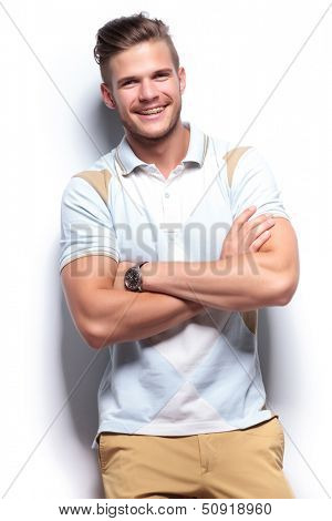 young casual man laughing while holding his arms crossed. on white background