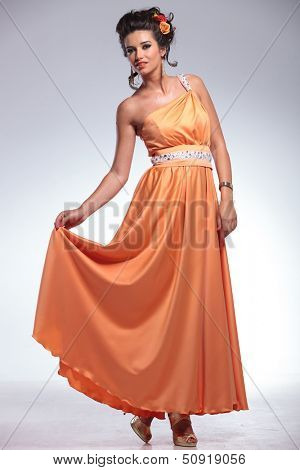 full length photo of a young fashion woman holding up her dress with one hand while looking into the camera. on gray background