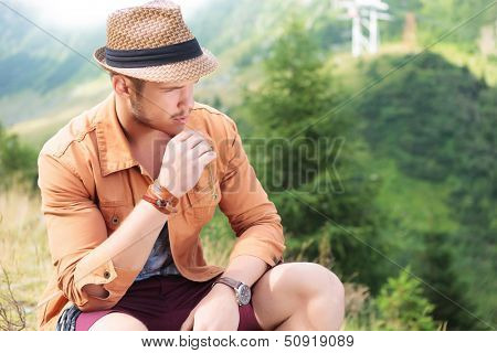 young casual man sitting in the nature with a straw in his mouth and looking away from the camera