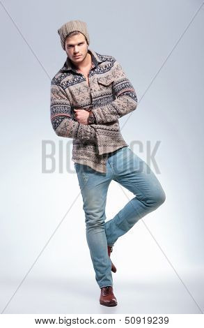 full length picture of casual young man balancing on one leg and looking at the camera while holding hand inside jacket. on light gray background
