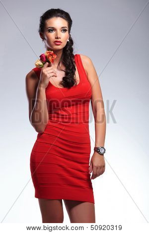 young beauty woman holding some flowers and looking away from the camera. on gray background