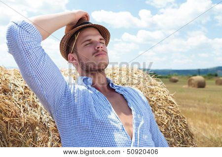 young casual man leaning back on a haystack while holding his hat and a straw behind his ear and his eyes closed