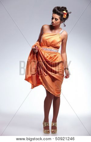 full length portrait of a young fashion woman lifting her dress up with a hand while looking down, away from the camera. on gray background