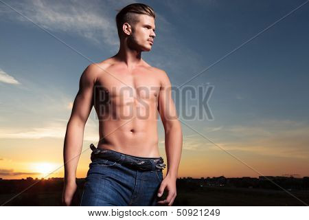 young topless man outdoor looking to his side, away from the camera with the sunset behind