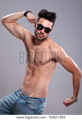 topless young man showing off with his muscles, flexing his arms. on gray background