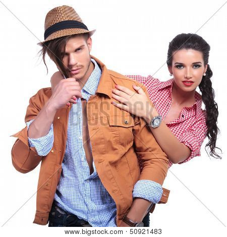 young casual couple looking into the camera while the man pulls down on his hair and the woman holds him by the shoulders from behind. on white background