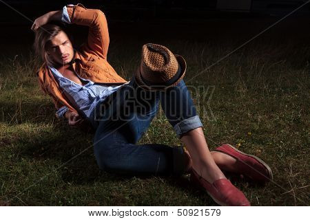 casual young man laying in the grass with his hat on his knee and his hand on his head while looking at the camera with a straw in his mouth