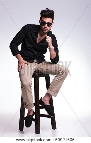full length photo of a young fashion man sitting on a chair and looking into the camera with his eyebrows raised. on a light background