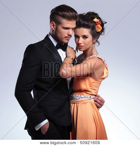 closeup portrait of a young fashion couple embracing while the woman is looking at the camera and the man is holding a hand in his pocket. on gray background