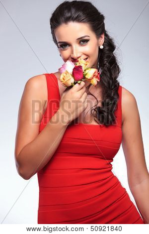 young beauty woman smiling while smelling some roses and looking into the camera. on gray background