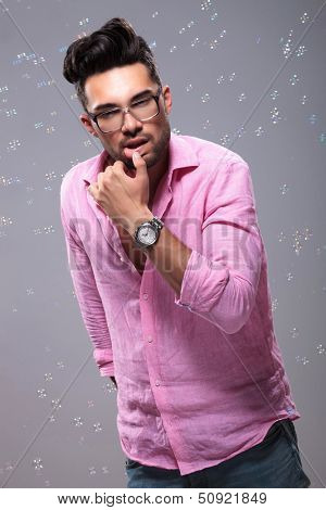 young fashion man sensually touching his lower lip with hi thumb while bubbles float around him. on a gray background