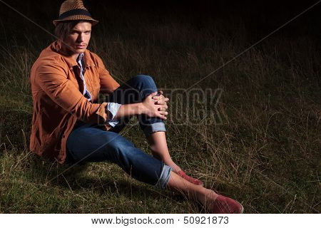 casual young man sitting outdoor and holding his hands on his knee while looking into the camera