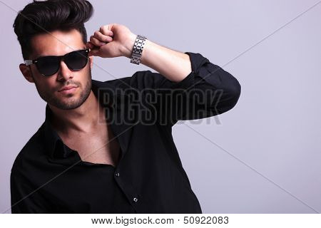 closeup portrait of a young fashion man posing with his hand on his sunglasses while looking at the camera. isolated on a gray background