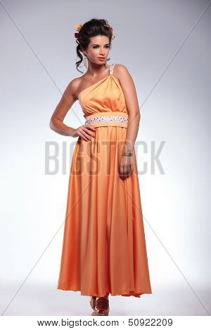 full length picture of a young fashion woman looking away while holding her hand on her hip. on gray background