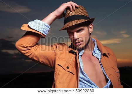 casual young man standing outdoor with a hand on his hat and a straw in his mout while looking away from the camera with the sunset behind