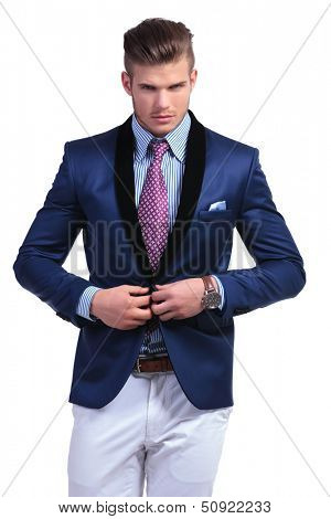 young business man unbuttoning his suit jacket while looking into the camera. on a white background