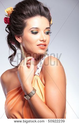 closeup of a young fashion woman looking to her side, away from the camera. on gray background