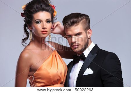 closeup of a young fashion couple looking into the camera. on gray background