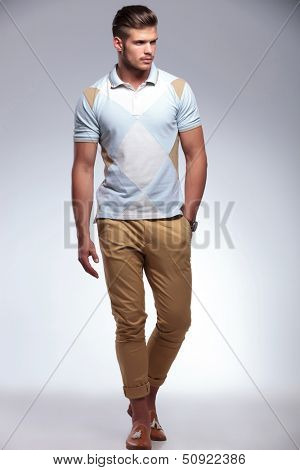 full length photo of a young casual man walking with a hand in his pocket and looking away from the camera. on gray background