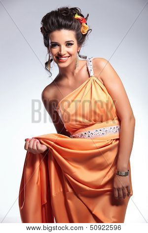 young fashion woman smiling for the camera while holding up her dress with one hand. on gray background