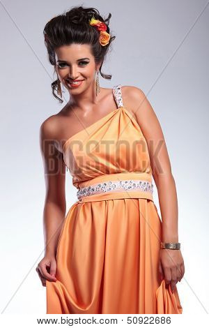 young fashion woman smiling for the camera while holding her dress with both hands. on gray background