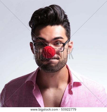 closeup picture of a young fashion man wearing a red nose and holding his breath while looking at the camera. on a light background