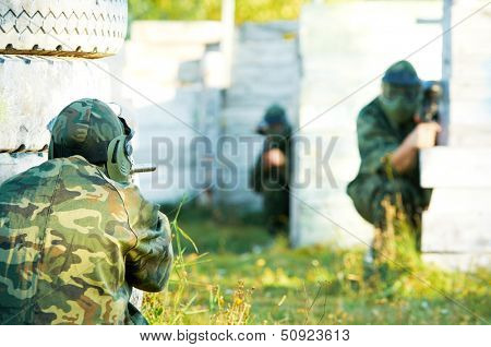 Two paintball sport players in prootective uniform and mask aiming and shoting with gun outdoors