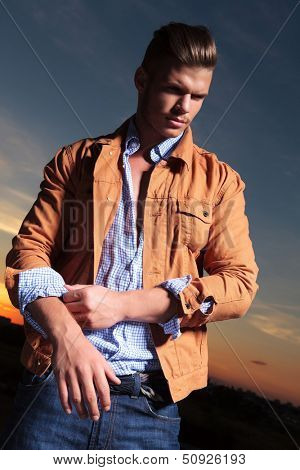casual young man standing outdoor and pulling up his sleeve while looking away from the camera with the sunset behind