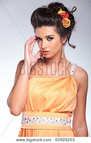 young fashion woman posing with her hand at her temple while looking into the camera. on gray background